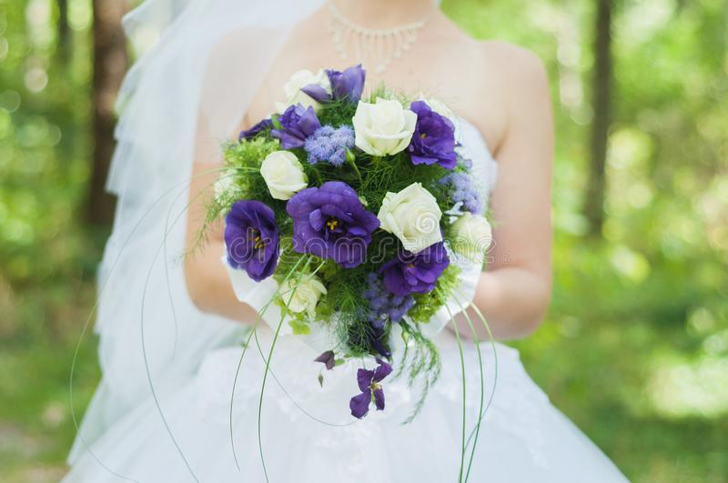 Bride after the wedding ceremony in the sun park holds a beautiful bouquet royalty free stock photo