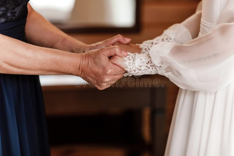 Bride on wedding day holding her mother`s hands. an old woman holds her young daughter married stock image