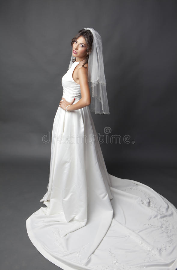 Bride in wedding dress. Studio portrait of a young bride wearing white wedding dress with veil, taken from above and looking up at camera stock photos