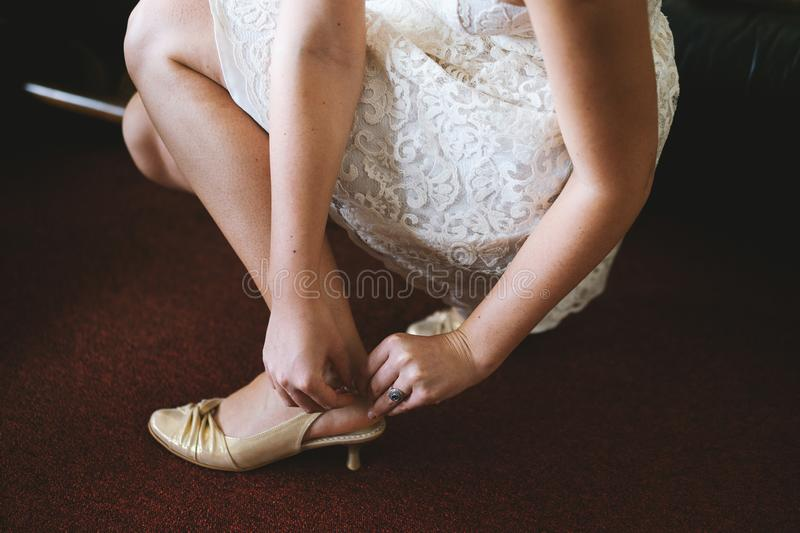 Bride sitting and putting on shoes royalty free stock photo