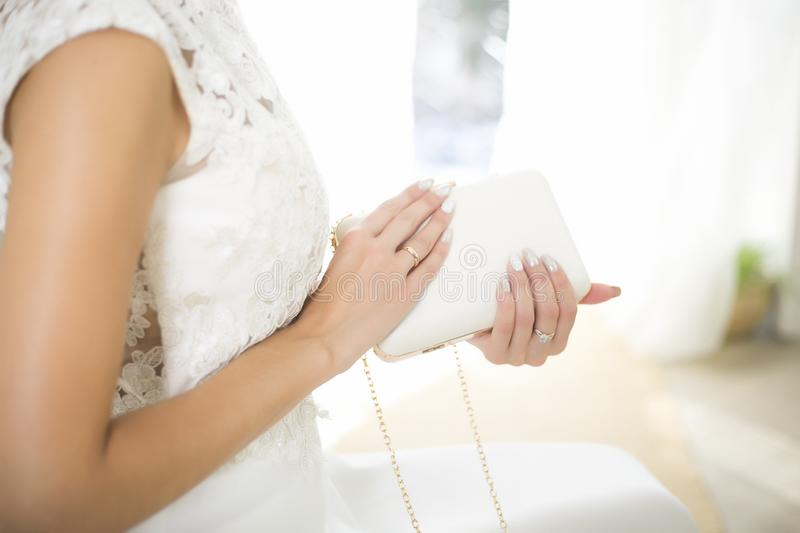 Bride in a wedding dress holds in hand a white bag. Beautiful manicure. Wedding day. Wedding rings.  stock photos