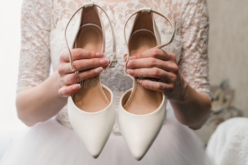The bride in a wedding dress holds white shoes in well-groomed hands with a beautiful manicure.  royalty free stock photo