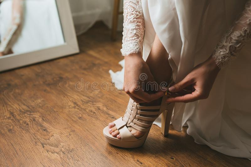 The bride in a wedding dress on morning preparation dresses beautiful beige shoes sandals close-up. Wooden background royalty free stock photography