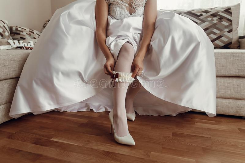 Bride in wedding dress putting on stockings silk garter, wedding. Morning preparation concept. getting ready, dressing lingerie, boudoir . space for text royalty free stock photography