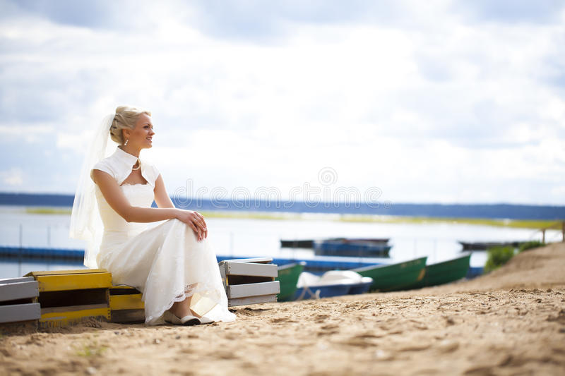 Bride in wedding dress. Sitting on a bench by the lake stock images