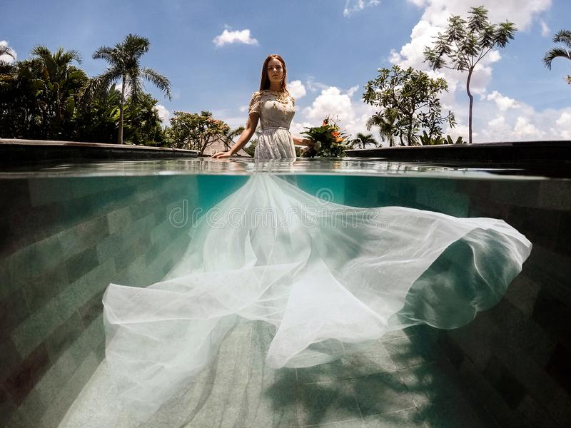 Bride in a wedding dress in a swimming pool royalty free stock images
