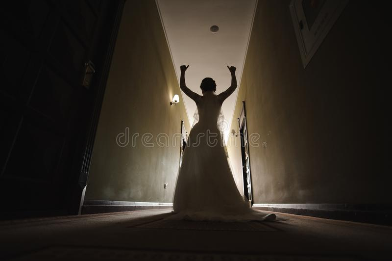 Bride in wedding dress and veil walking down the hallway of the hotel stock photography
