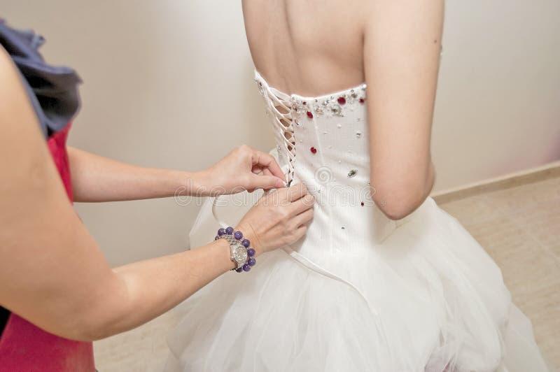 Bride wedding dresses. Bride and bridesmaids help fixed wedding dresses stock image