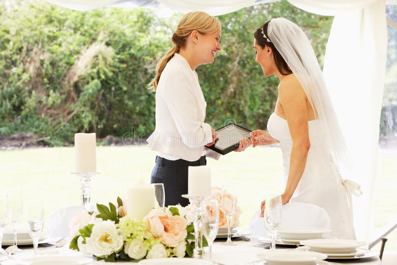 Bride With Wedding Planner In Marquee. Smiling To Each Other royalty free stock photography