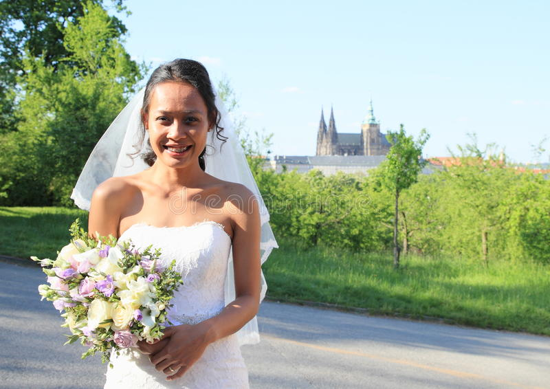 Bride on wedding in Prague. Smiling bride in white dress with veil holding flower with yellow and purple blossoms - Papuan girl on wedding day with Prague Castle stock image
