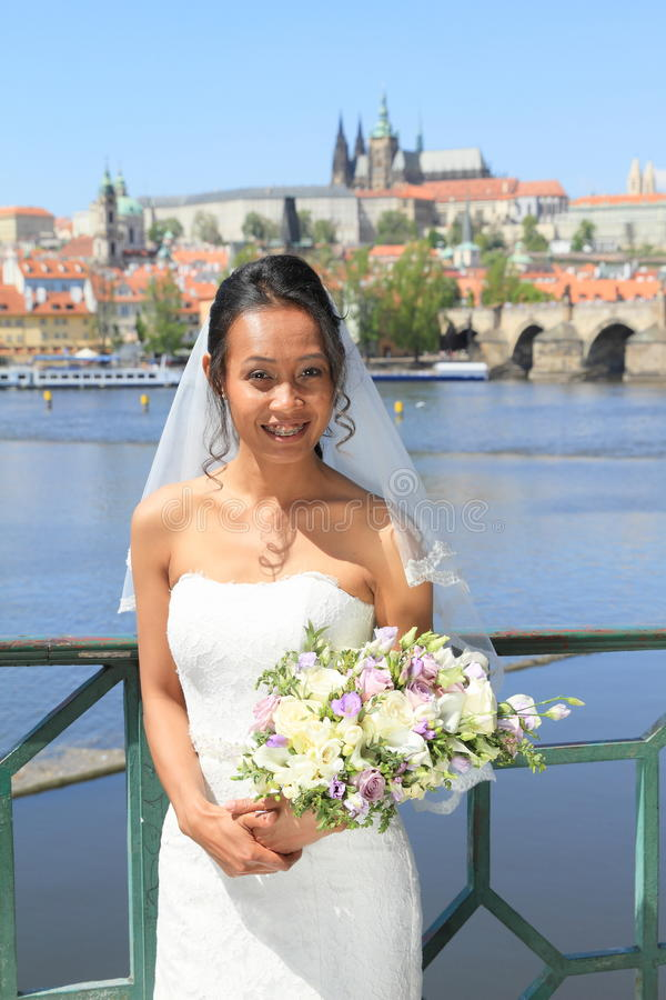 Bride on wedding in Prague. Smiling bride in white dress with veil holding flower with yellow and purple blossoms - Papuan girl on wedding day standing in front stock image