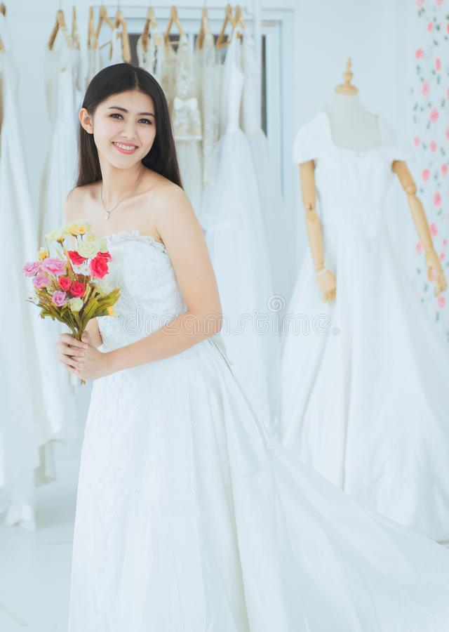 Bride in white dress holding a bouquet on hand for wedding,Beautiful asian woman smiling and happy,Romantic and sweet moment royalty free stock photography