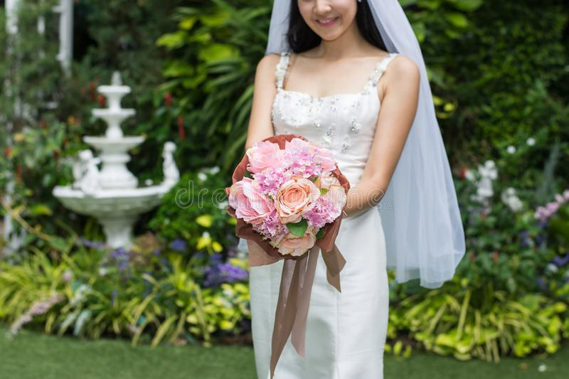 Bride in a white dress holding wedding bouquet of flowers with ribbons stock images