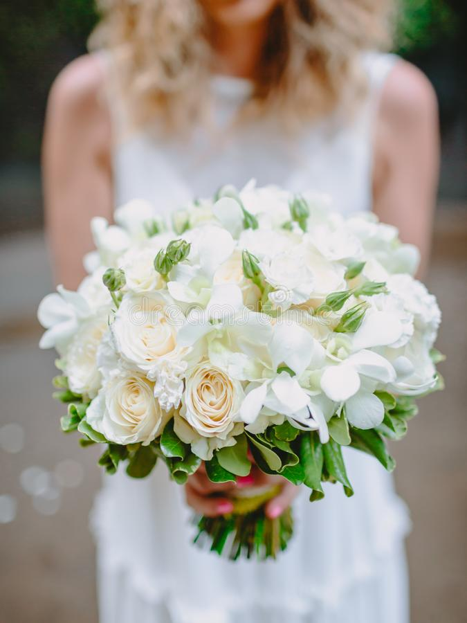 Bride in white dress holds a bouquet with roses flowers. Wedding day and ceremony. Bride in white dress holds a bouquet with roses flowers. Wedding day stock photo