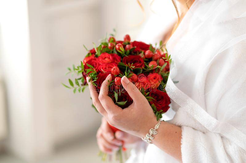 The bride in a white dress holds in her hands a stylish wedding bouquet of red roses. Wedding details stock image