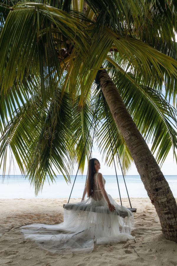 A bride in a white dress is riding on a swing under a big palm tree royalty free stock image
