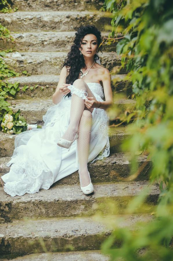 Bride in white dress sit on steps outdoor. Woman wear lace garter on leg. woman in stockings lingerie on wedding royalty free stock photo