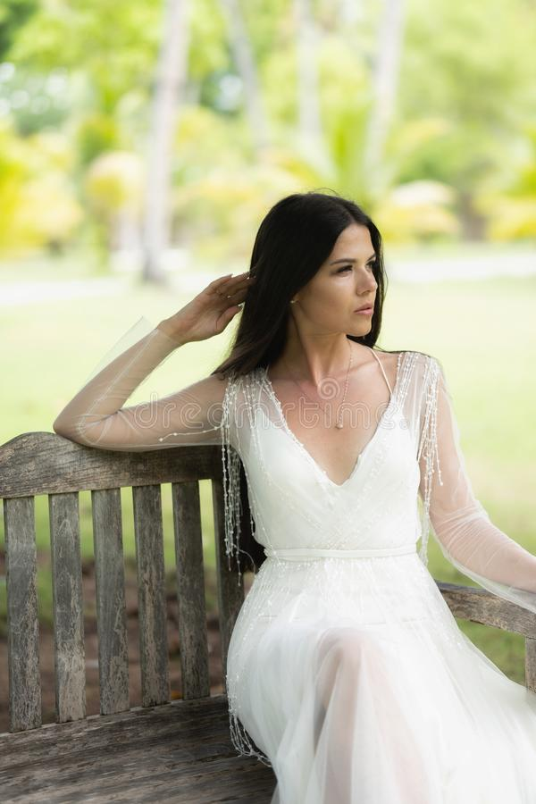A bride in a white dress is sitting on an old royalty free stock images