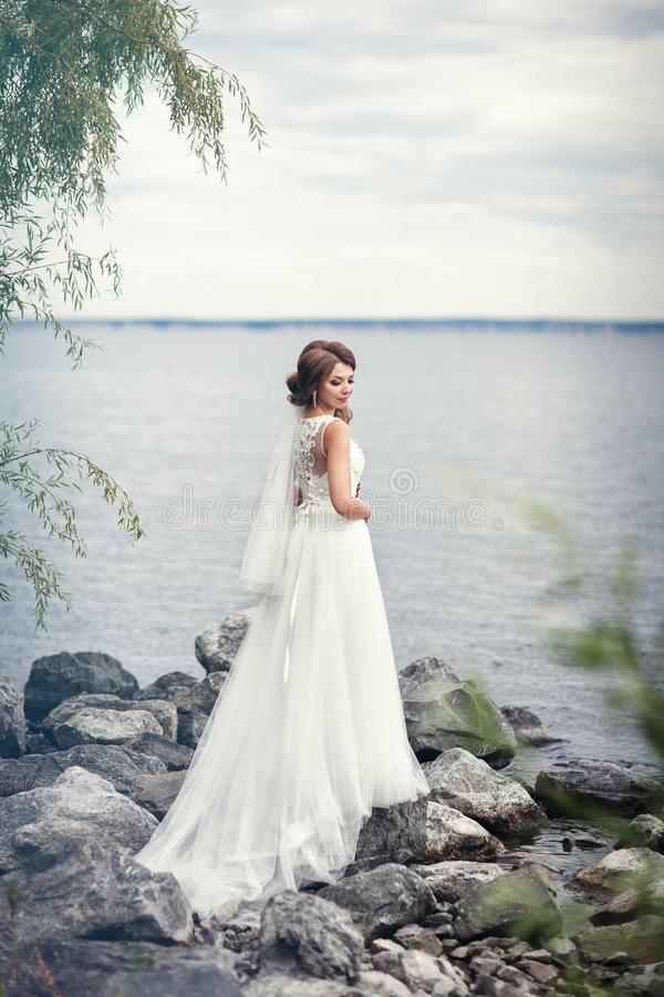 The bride in a white dress on the stones near the river stock images