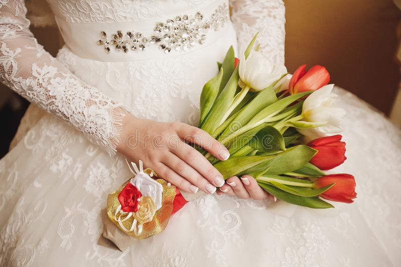 The bride in a white elegant lace wedding dress is holding a beautiful wedding bouquet of white and red tulips. Wedding theme royalty free stock images