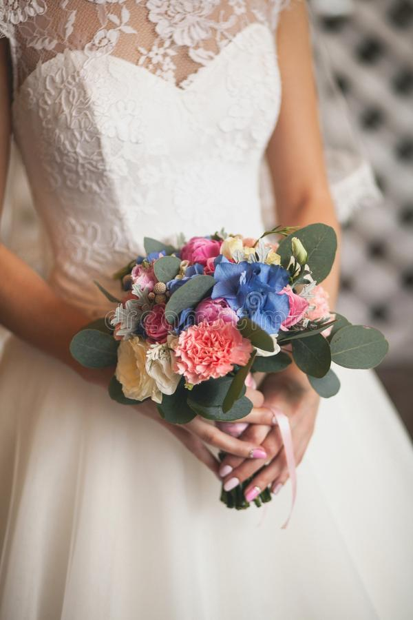 The bride in a white elegant wedding dress is holding a beautiful wedding bouquet of different flowers and green leaves. Wedding theme stock photo