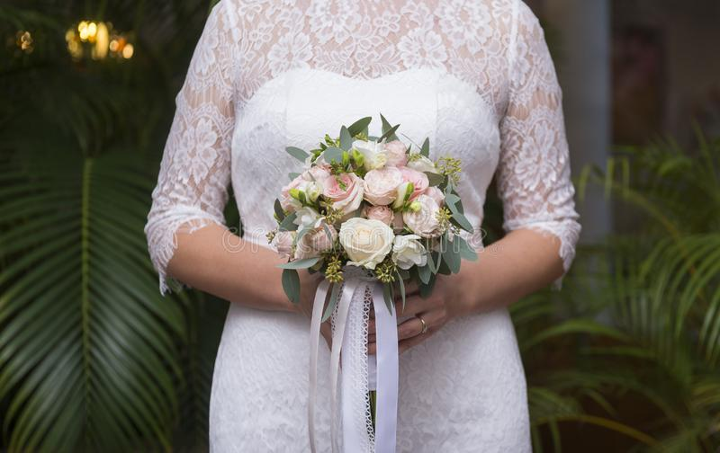 Bride in a white lace dress holds a bouquet of pink roses on a green foliage background. Bride in a white lace dress holds a bouquet of pink roses with greens stock photo