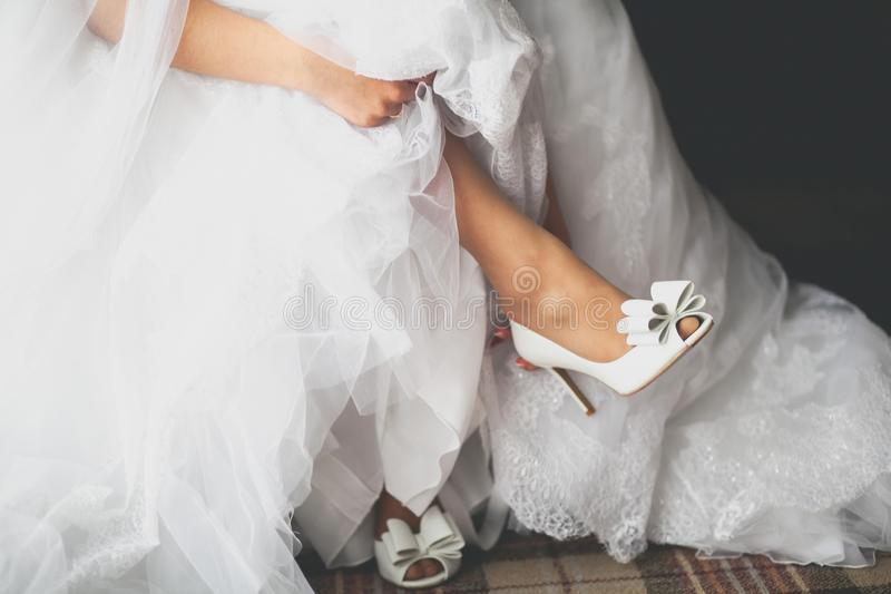 The bride in a white magnificent dress puts on a foot white beautiful Shoe, holding the hem. Preparation of the bride for the stock photography