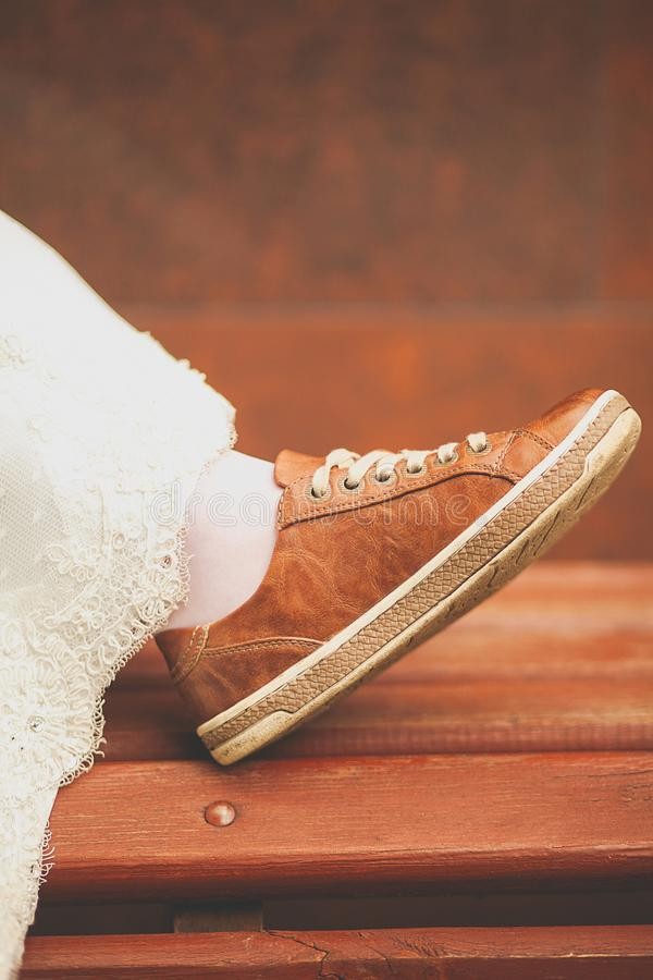 Bride in white wedding dress and brown sneakers or sports shoes. Women`s foot in a sneaker, on a wooden painted bench, close-up, stock photography