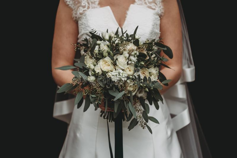 Bride with a white wedding dress holding a beautiful flower bouquet against a black background. A bride with a white wedding dress holding a beautiful flower royalty free stock image