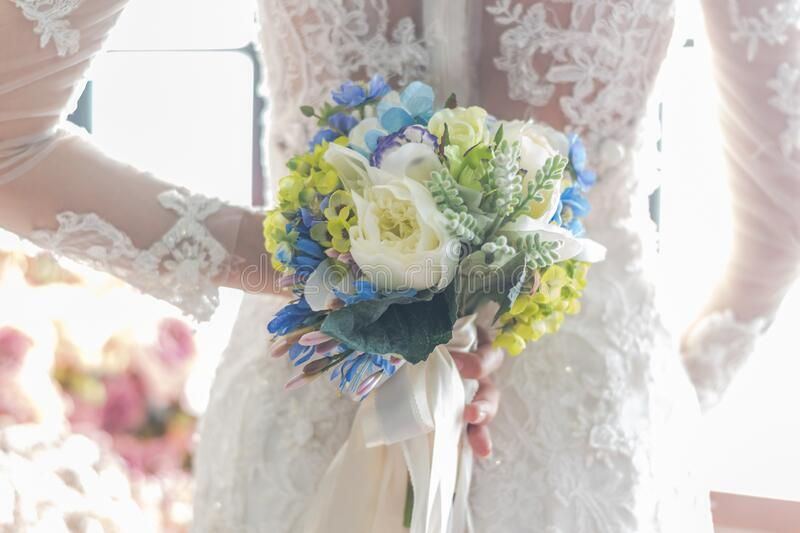 Bride in white wedding dress holding flower bouquet for elegant marriage ceremony concept.  stock image