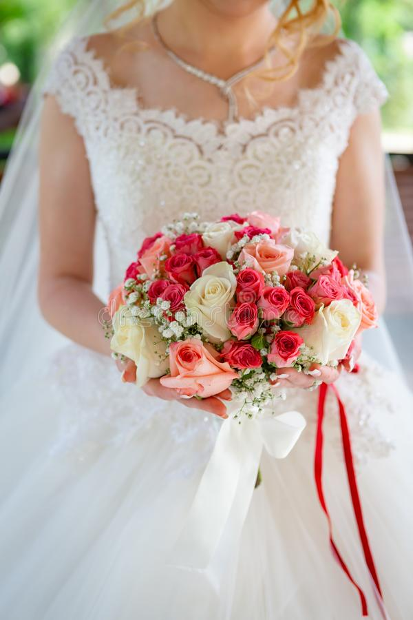 The bride in a white wedding dress with a red ribbon on her belt, with a wedding bouquet of roses in her hands. stock photos