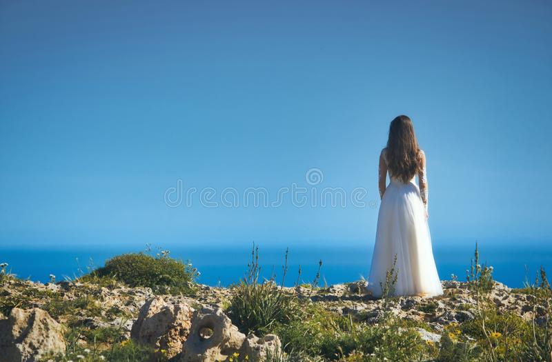 A bride in a white wedding dress standing on a cliff edge looking out to sea royalty free stock photos