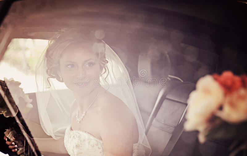 Bride in window. A beautiful bride smiling in a limousine through rainy window
