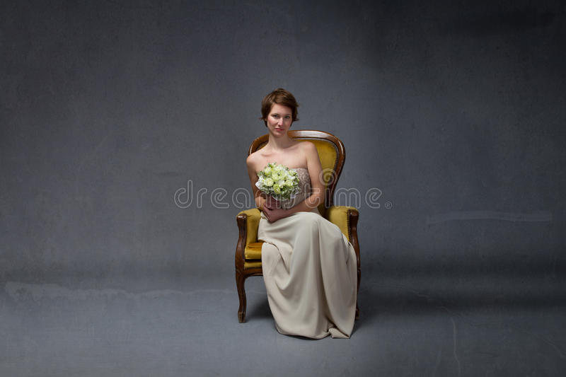Bride woman sitting on yellow sofa stock photography