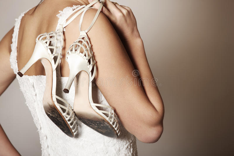Bride with worn-out shoes. A portrait of the back of the bride carrying worn-out shoes royalty free stock images