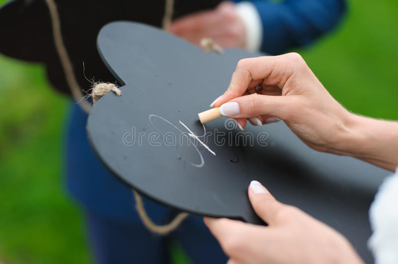 Bride writes with chalk on a board stock photo