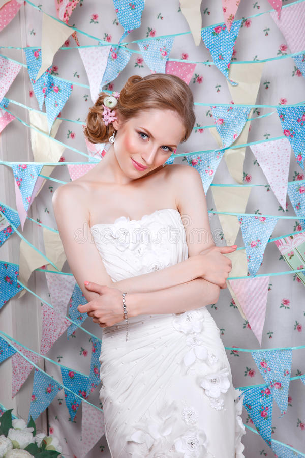Bride.Young fashion model with perfect skin and make up, flowers in hair. Beautiful woman with makeup and hairstyle in bedroom. Happy Bride waiting groom royalty free stock photography