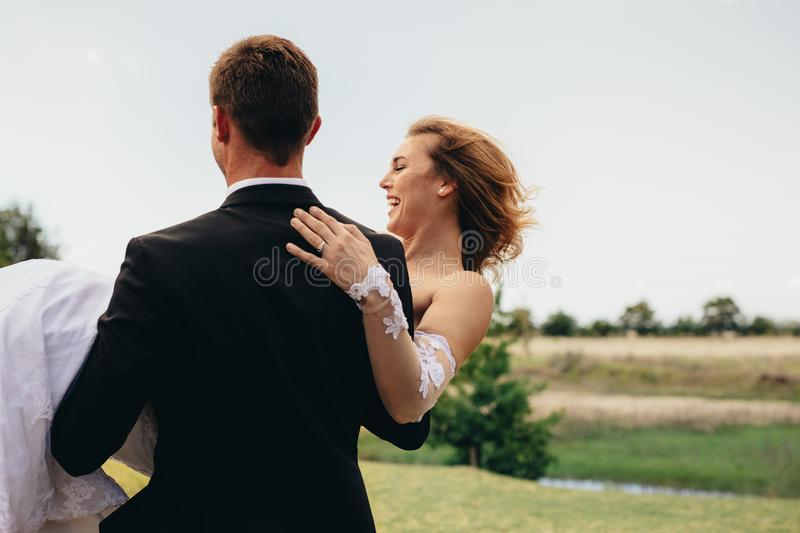 Bridegroom carrying bride on wedding day royalty free stock images