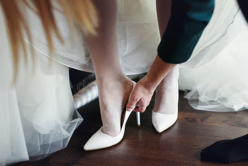 Bridemaid hjälper bruden att sätta på skor royaltyfria bilder