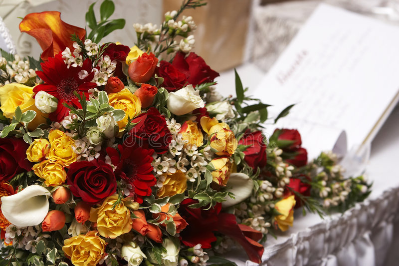 Brides bouquet with a guest book in the background royalty free stock photography
