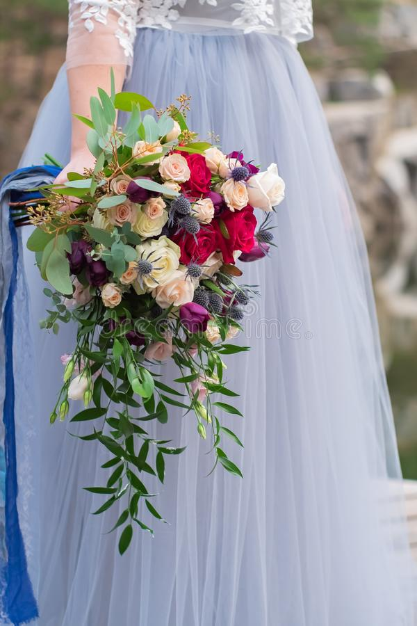 The brides hand holds a wedding bouquet of roses and feverweed on the background of a wedding dress royalty free stock image