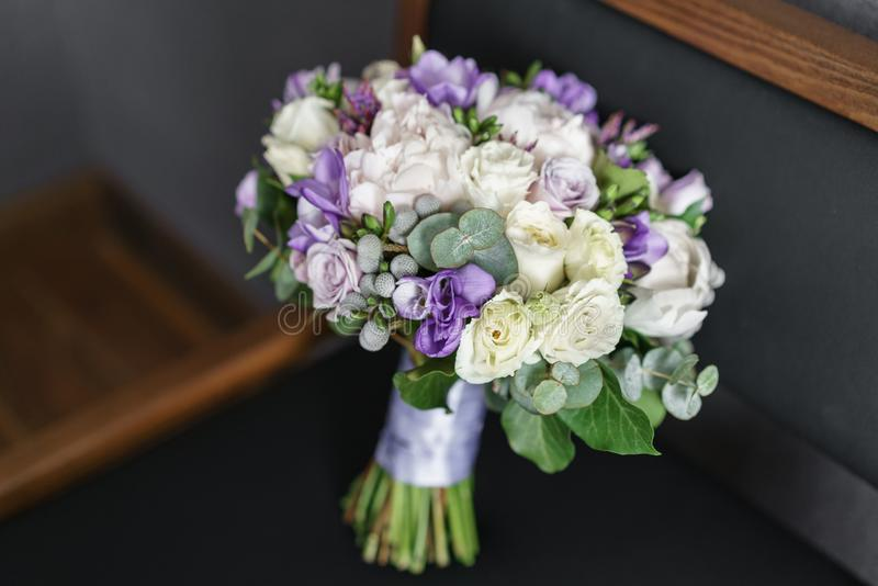Brides wedding bouquet with peonies, freesia and other flowers on black arm chair. Light and lilac spring color. Morning. Brides wedding bouquet with peonies stock photos
