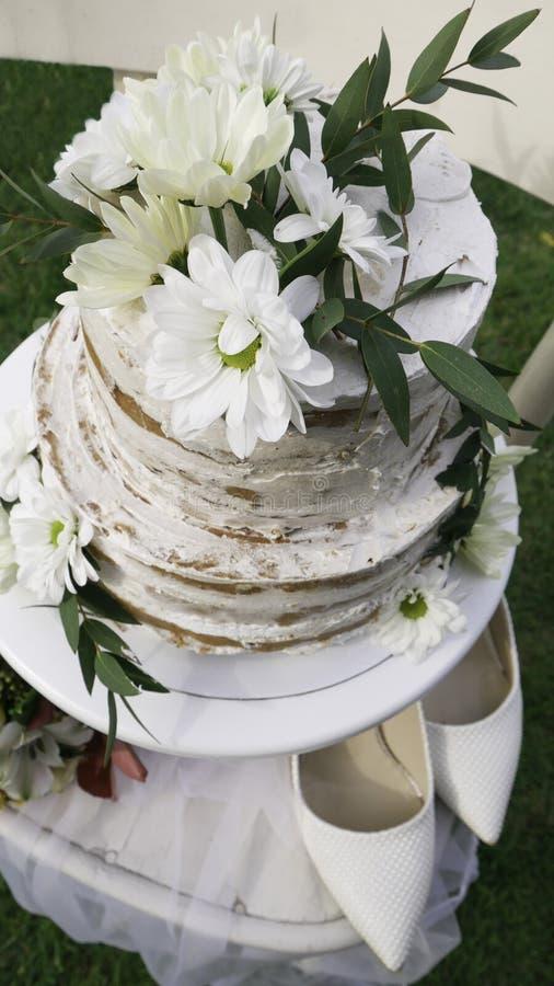 Brides White Shoes i dwupoziomowe torty weselne na drewnianym krześle - widok z góry obrazy royalty free