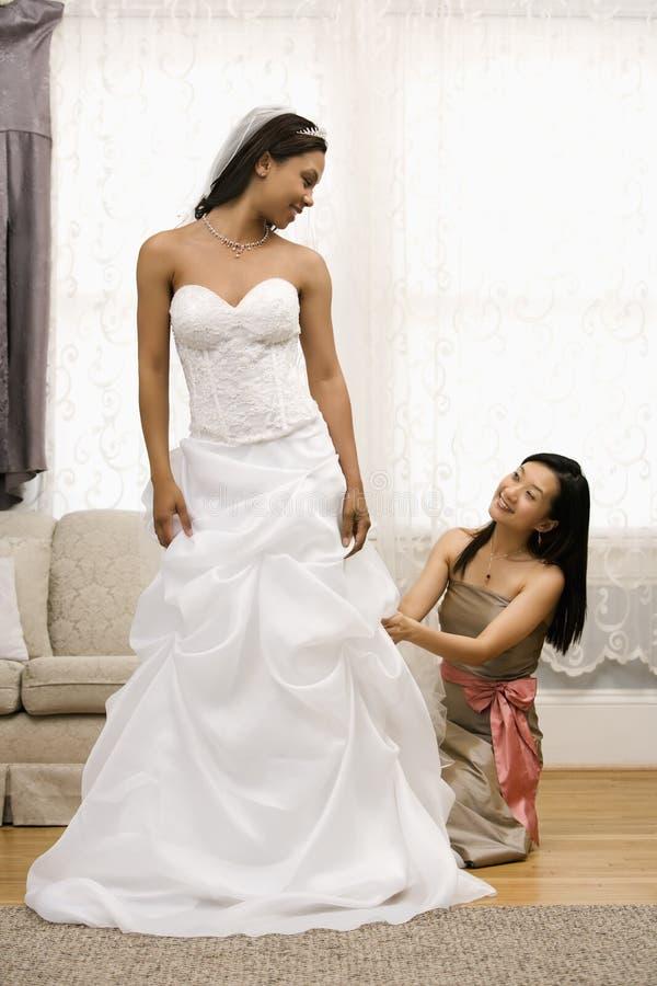 Bridesmaid adjusting dress. Asian bridesmaid fixing African-American bride's dress stock photos