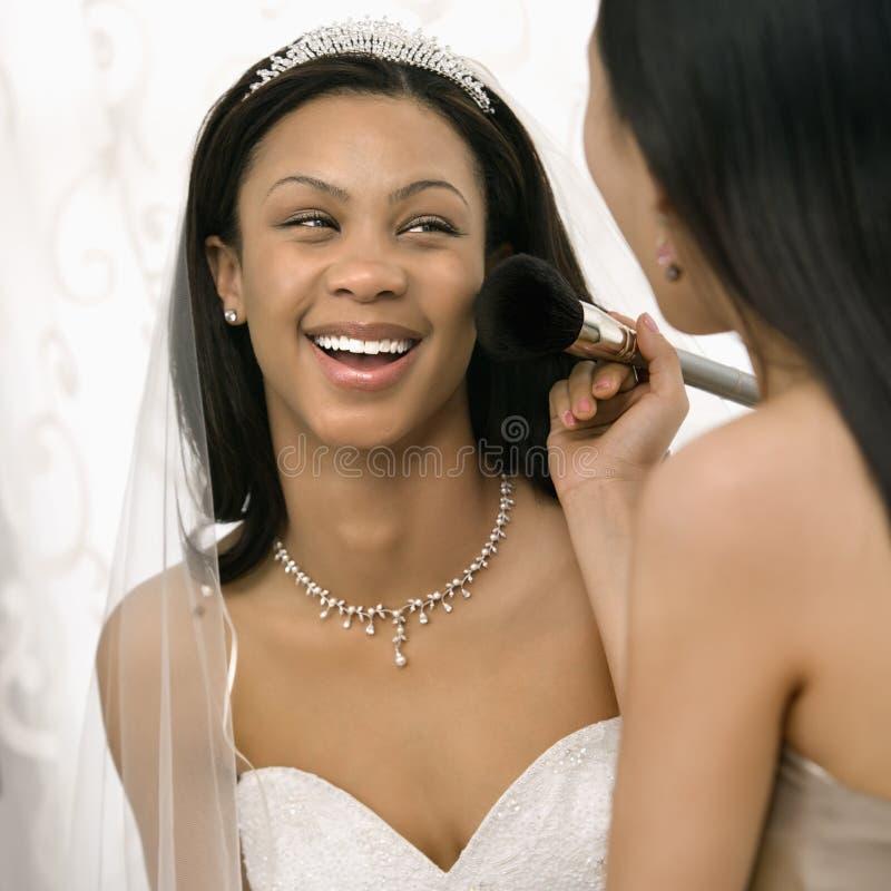 Bridesmaid applying makeup. Asian bridesmaid applying makeup to African-American bride stock photo