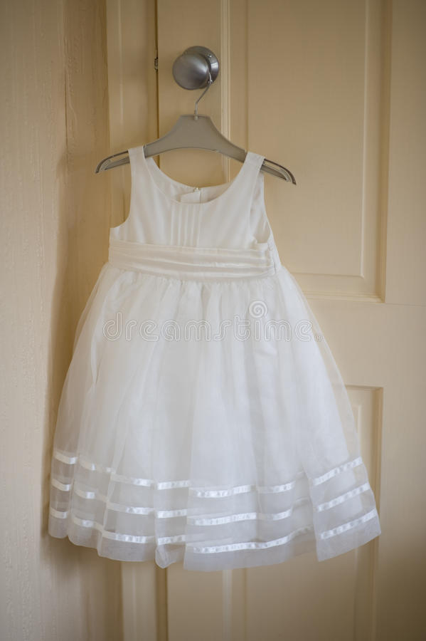 Bridesmaid or flowergirl dress for a wedding. White bridesmaid or flowergirl dress before a wedding stock photography
