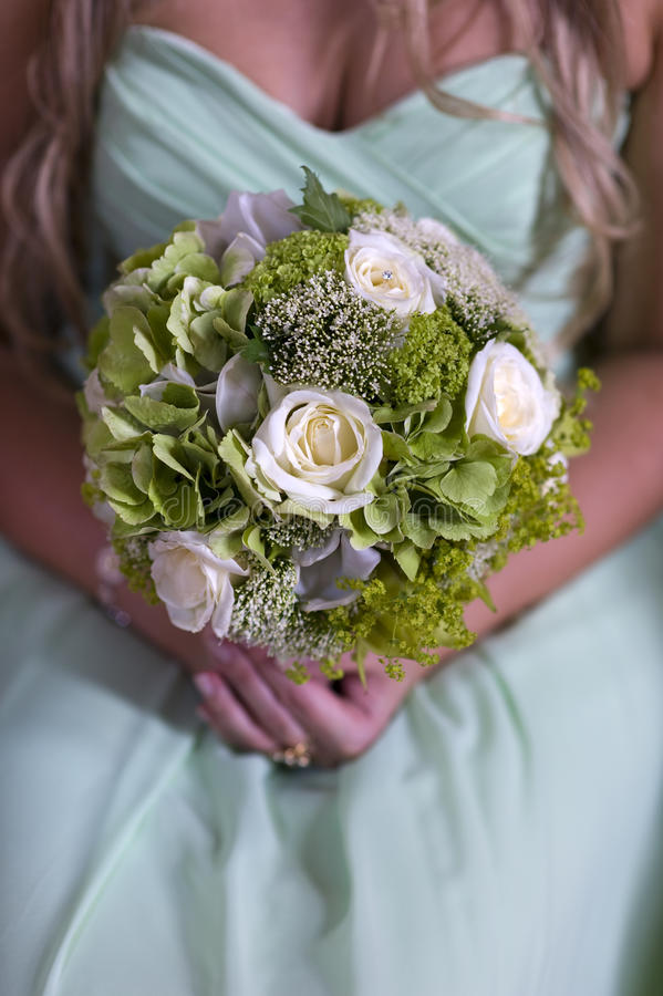 Bridesmaid in green with wedding bouquet royalty free stock images