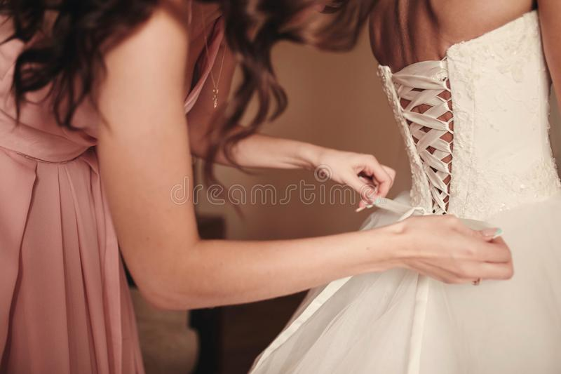 Bridesmaid helping bride fasten corset close-up and getting her dress, preparation concept in morning for wedding day stock photo