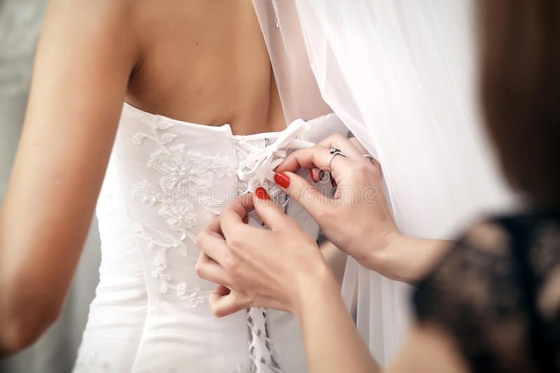 Bridesmaid helps bride to put on a wedding dress. stock photography
