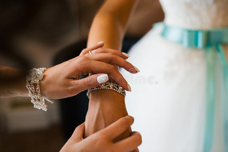 Bridesmaid helps to tie a bow on a festive white dress of the bride on the wedding day. Girl straightens his hands bracelet jewelry on the bride`s wrist stock photo